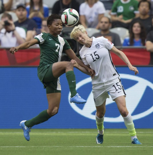 Nigeria's Esther Sunday, left, and United States' Megan Rapinoe vie for the ball during the first half of a FIFA Women's World Cup soccer game Tuesday, June 16, 2105, in Vancouver, British Columbia, Canada. (Darryl Dyck/The Canadian Press via AP)