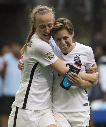 United States' Meghan Klingenberg and Becky Sauerbrunn celebrate their teams win over Nigeria at a FIFA Women's World Cup soccer match, Tuesday, June 16, 2015 in Vancouver, New Brunswick, Canada. (Jonathan Hayward/The Canadian Press via AP)