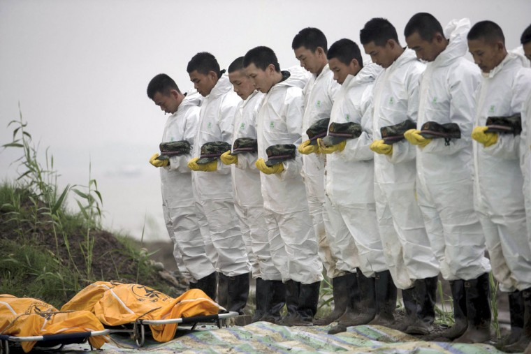 Rescuers observe a moment of silence for victims recovered from the capsized tourist ship in the Yangtze River in Jianli county in central China's Hubei province, Wednesday, June 3, 2015. Chinese authorities deployed scores more divers and a large crane as they escalated efforts Wednesday to recover more than 410 people believed to be trapped inside an overturned river cruise ship.(Chinatopix Via AP)