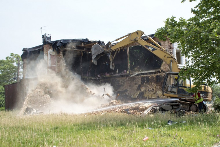 Crews continued to tear down the last of the vacant homes on Tivoly Avenue. (Tom Brenner / The Baltimore Sun)