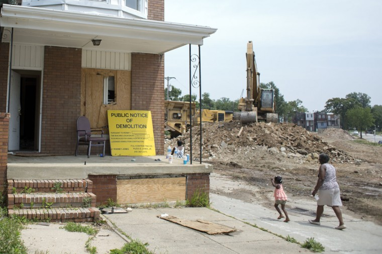 People pass by the last vacant home on Tivoly Avenue before its demolition, lead by the mayor's Vacants to Value program. To date, Vacants to Value has leveraged more than $107 million dollars in private investment to demolish or rehabilitate more than 3,000 vacant homes. Tom Brenner / The Baltimore Sun.