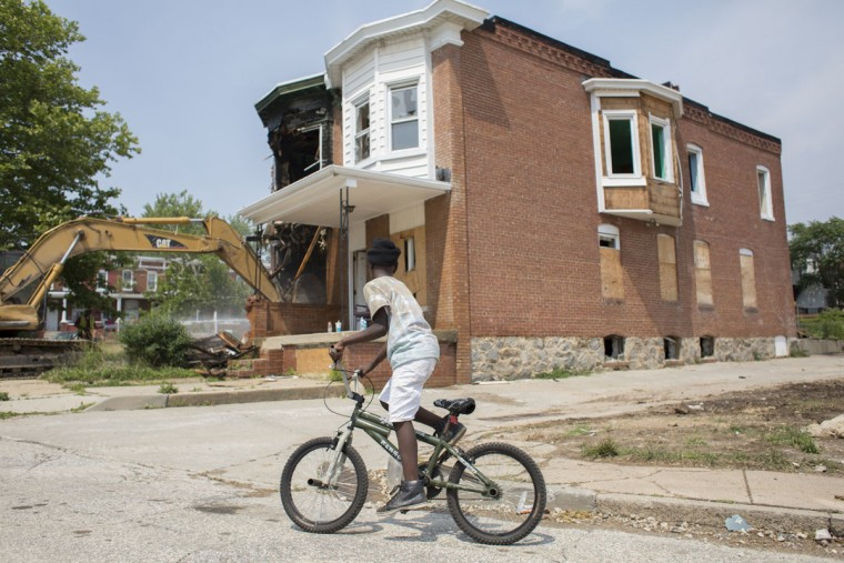 A boy is seen riding his bike around the demolition area of the last vacant home on Tivoly Avenue. The demolition effort was made by the mayor's Vacants to Value program. To date, Vacants to Value has leveraged more than $107 million dollars in private investment to demolish or rehabilitate more than 3,000 vacant homes. Tom Brenner / The Baltimore Sun.