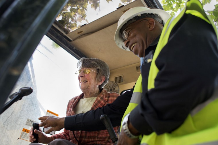 Councilwoman Mary Pat Clarke, left, operates a bulldozer with the help of Pless Jones, right, to begin the demolition process of the final vacant building on Tivoly Avenue. The demolition effort was made by the mayor's Vacants to Value program. To date, Vacants to Value has leveraged more than $107 million dollars in private investment to demolish or rehabilitate more than 3,000 vacant homes. Tom Brenner / The Baltimore Sun.