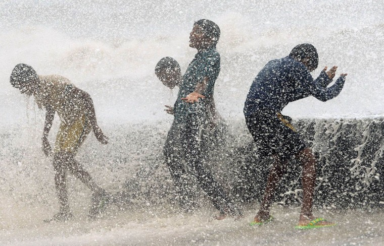 Indian youths play in breaking waves on the seafront during high tide in Mumbai. (Punit Paranipe/Getty Images)