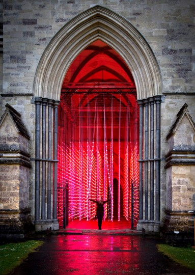 Roz Mitchell, marketing manager, explores the new Squidsoup light installation, Enlightenment, in the North Porch of Salisbury Cathedral on June 12, 2015 in Salisbury, England. The installation, which is made up of around 6000 points of colour changing light bulbs suspended from the ceiling, is part of the Cathedral's celebrations for the 800th anniversary of the Magna Carta. (Photo by Matt Cardy/Getty Images)