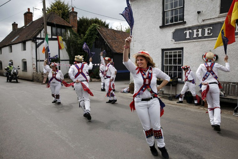 "Wickham Morris dancers perform during the Clogg and Morris Festival, in Odiham, some fifty miles west of London on May 23, 2015, as part of the 800th anniversary celebrations of the signing of the Magna Carter. The Magna Carta, Latin for ""the Great Charter,"" was a charter agreed by King John of England on 15 June 1215, and was drafted by the then Archbishop of Canterbury, Stephen Langton, to make peace between the unpopular King and a group of rebel barons, and promising amongst other things, the protection of church rights. (AFP Photo/Adrian Dennis)"