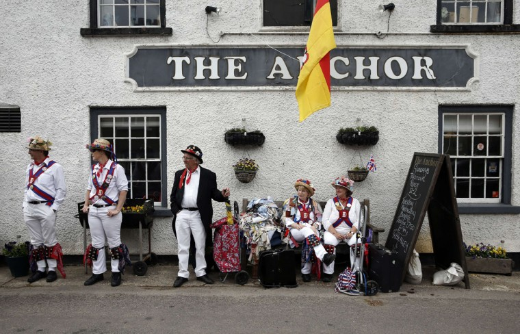 "Morris dancers stand outside The Anchor pub during the Clogg and Morris Festival, in Odiham, some fifty miles west of London on May 23, 2015, as part of the 800th anniversary celebrations of the signing of the Magna Carter. The Magna Carta, Latin for ""the Great Charter,"" was a charter agreed by King John of England on 15 June 1215, and was drafted by the then Archbishop of Canterbury, Stephen Langton, to make peace between the unpopular King and a group of rebel barons, and promising amongst other things, the protection of church rights. (AFP Photo/Adrian Dennis)"