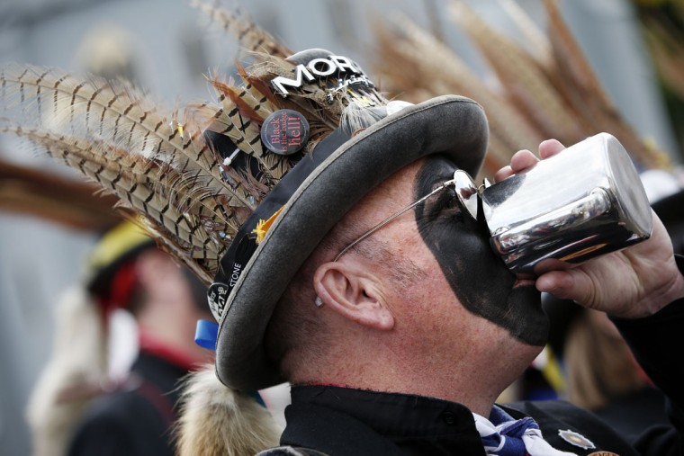 "A Hook Eagle Morris Man drinks from a tankard after performing a dance during the Clogg and Morris Festival, in The Bury, Odiham, some fifty miles west of London on May 23, 2015, as part of the 800th anniversary celebrations of the signing of the Magna Carter. The Magna Carta, Latin for ""the Great Charter,"" was a charter agreed by King John of England on 15 June 1215, and was drafted by the then Archbishop of Canterbury, Stephen Langton, to make peace between the unpopular King and a group of rebel barons, and promising amongst other things, the protection of church rights. (AFP Photo/Adrian Dennis)"