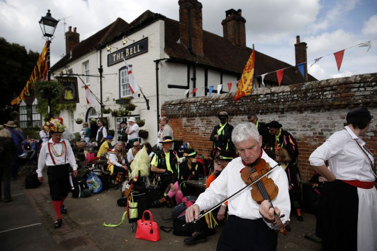 "Morris dancers stand gather in The Bury during the Clogg and Morris Festival, in Odiham, some fifty miles west of London on May 23, 2015, as part of the 800th anniversary celebrations of the signing of the Magna Carter. The Magna Carta, Latin for ""the Great Charter,"" was a charter agreed by King John of England on 15 June 1215, and was drafted by the then Archbishop of Canterbury, Stephen Langton, to make peace between the unpopular King and a group of rebel barons, and promising amongst other things, the protection of church rights. (AFP Photo/Adrian Dennis)"
