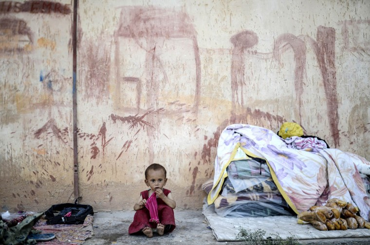 A Syrian refugee baby sits in front of a wall near the Turkish border post of Akcakale, province of Sanliurfa. The first Syrian refugees returned to the border town of Tal Abyad from Turkey after it was liberated from the Islamic State (IS) group, an AFP journalist reported. Kurdish forces took the strategic town on Tuesday after several days of intense fighting, which sparked an exodus of more than 23,000 refugees into neighbouring Turkey. (Bulent Kilic/Getty Images)
