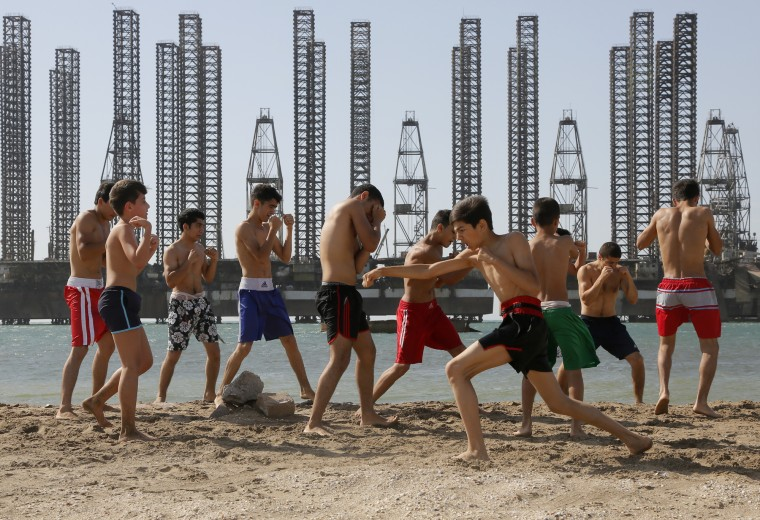 Teenagers belonging to a kickboxing school attend a training session at a beach on the Caspian Sea with Soviet era oil platforms in the background, Baku, Azerbaijan. The 2015 European Games are being held in Baku until June 28. (Dmitry Lovetsky/Associated Press)