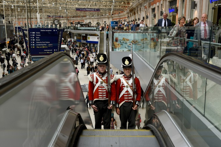 Battle of Waterloo reenactors travel the escalators at Waterloo Station after they attended the unveiling of a memorial plaque by the current Duke of Wellington, Brigadier Arthur Wellesley in London, England. The bronze plaque, measuring 65cm across, depicts Nike the Greek goddess of Victory and has been cast by the London Mint Office to commemorate the soldiers that died on the battlefield at Waterloo in its 200th anniversary year. (Mary Turner/Getty Images)