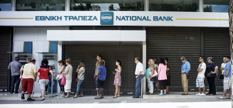 Greeks queue in front of the National Bank to use ATM to withdraw cash as Parliament holds an emergency session for the government's proposed referendum in Athens, Greece. Greece's fraught bailout talks with its creditors took a dramatic turn early Saturday, with the radical left government announcing a referendum in just over a week on the latest proposed deal. (Milos Bicanski/Getty Images)