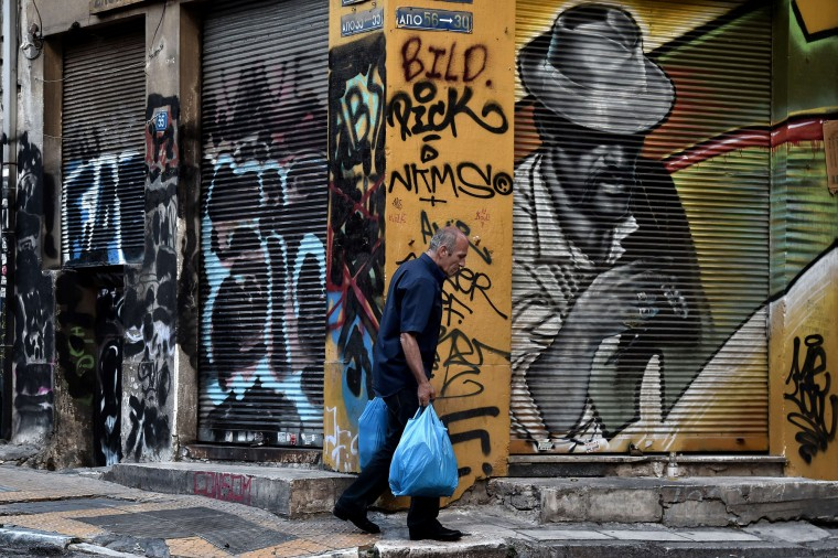 A man walks past graffiti on the streets of central Athens. Greece hurtled towards default and a possible euro exit after Europe responded to the leftist government's announcement of a surprise referendum by refusing to extend Athens's desperately needed bailout. (Aris Messinis/AFP-Getty Images)
