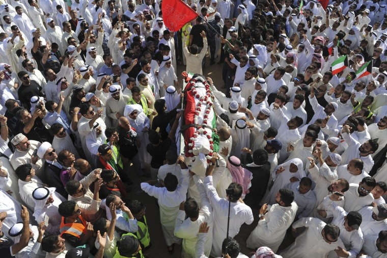 Thousands of Sunnis and Shiites from across the country take part in a mass funeral procession for 27 people killed in a suicide bombing that targeted the Shiite Imam Sadiq Mosque a day earlier, at the Grand Mosque in Kuwait City, Kuwait. Police in Kuwait said they are interrogating a number of suspects with possible links to the bombing, which was claimed by an affiliate of the Islamic State group. (Associated Press)