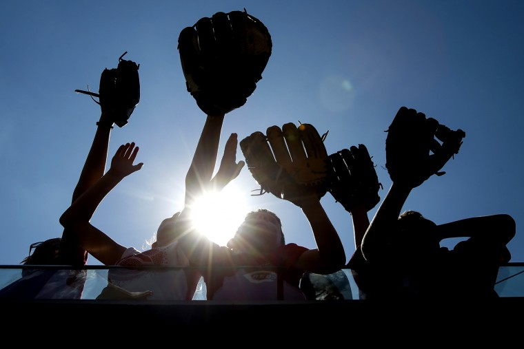 Young fans plead for baseballs next to the Cincinnati Reds dugout during a baseball game against the Philadelphia Phillies in Cincinnati. The Reds won 5-2. (John Minchillo/Associated Press)