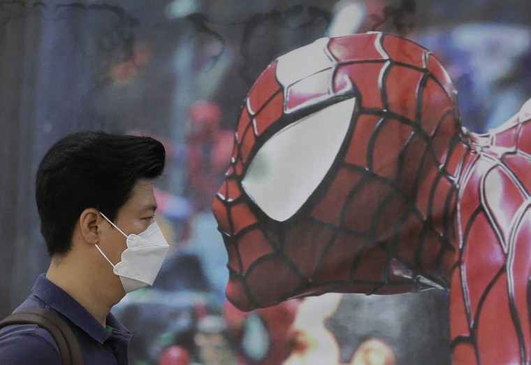 A South Korean man wearing a mask as a precaution against the Middle East Respiratory Syndrome virus walks by a Spider-Man poster advertising a musical for children in Seoul, South Korea. MERS has infected nearly 100 and caused nine deaths in South Korea, but experts say the virus mainly spreads through close contact with an infected person. (Ahn Young-joon/Associated Press)