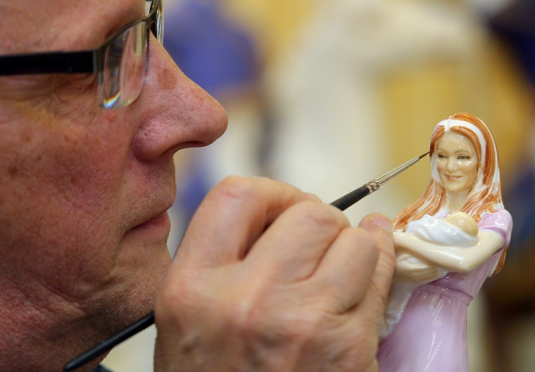 Master Painter Tom Mason works on a figurine designed by artist Neil Faulkner of HRH Princess Charlotte of Cambridge held by her mother Catherine, Duchess of Cambridge, standing alongside Prince George, at Waterford Wedgewood Royal Doulton factory in Barlaston in Stoke-on-Trent, England.The hand painted bone china figure, which is produced by Royal Doulton, will be launched as a limited edition of 3000 pieces and will be available from September 2015. (Dave Thompson/Getty Images)