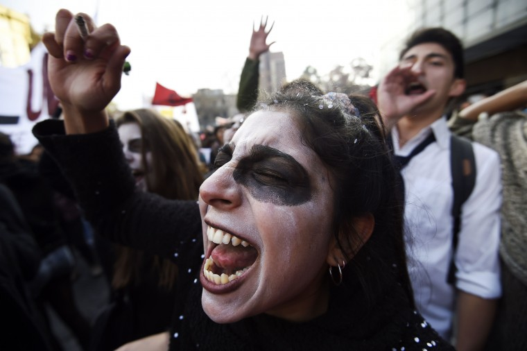 Demonstrators shout slogans as they clash with the police at the end of a march of students and teachers protesting against what they call inadequate education reforms, in Santiago on the eve of the start of the 2015 Copa America continental football tournament here in Chile. Thousands of demonstrators took to the streets of Santiago to condemn President Michelle Bachelet's reforms, claiming they fall short of overhauling an unequal education system inherited from the 1973-1990 dictatorship of late ruler Augusto Pinochet. (Juan Barreto/AFP-Getty Images)