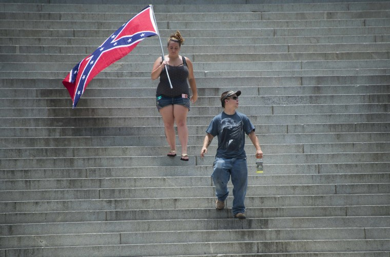 "Pro-confederate flag demonstrators walk down the steps of the South Carolina State House in Columbia, South Carolina. There has been a growing clamor for the flag -- branded ""a reminder of systemic oppression and racist subjugation"" by President Barack Obama on Friday -- to be removed from the grounds of the state house in Columbia. Once flown by the rebel army of the slave-owning South, the confederate flag is seen by some as a symbol of regional heritage, but by many more as an ugly reminder of racism's cruel legacy. (jim Watcson/AFP-Getty Images)"