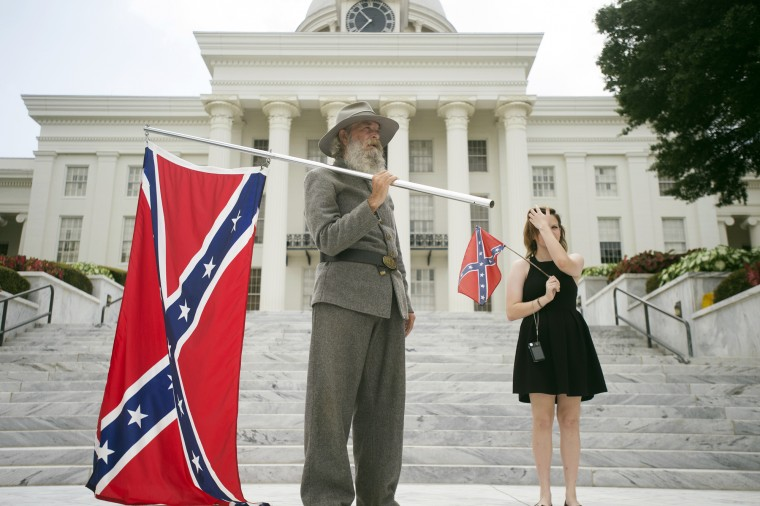 Dan Williams, 65, of Ashville, Ala., holds a Confederate flag while standing with his daughter Bonnie-Blue Williams, 15, in front of the Alabama State Capitol building during a Confederate flag rally in Montgomery, Ala. (Albert Cesare/The Montgomery Advertiser via AP)