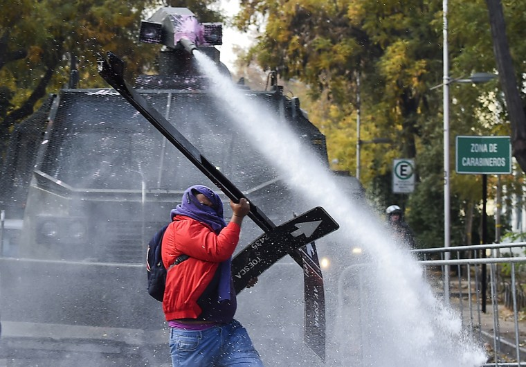 A demonstrator clashes with the police at the end of a march of students and teachers protesting against what they call inadequate education reforms, in Santiago, on June 10, 2015 on the eve of the start of the 2015 Copa America continental football tournament here in Chile. Thousands of demonstrators took to the streets of Santiago to condemn President Michelle Bachelet's reforms, claiming they fall short of overhauling an unequal education system inherited from the 1973-1990 dictatorship of late ruler Augusto Pinochet. (Luis Acosta/AFP-Getty Images)