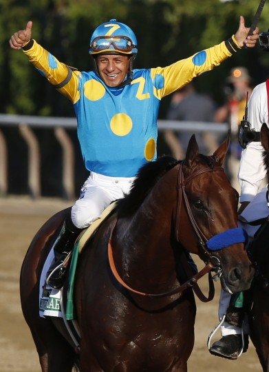 Victor Espinoza celebrates atop American Pharoah after winning the 147th running of the Belmont Stakes horse race at Belmont Park, Saturday, June 6, 2015, in Elmont, N.Y. American Pharoah is the first horse to win the Triple Crown since Affirmed won it in 1978. (Julio Cortez/Associated Press)