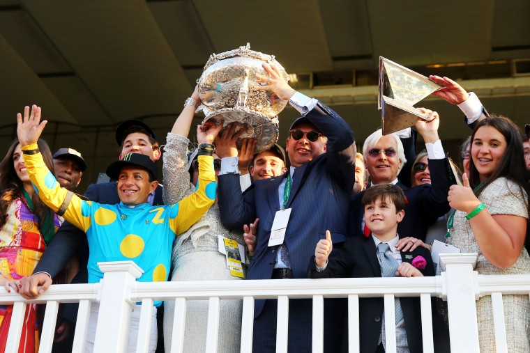 Victor Espinoza (L), jockey of American Pharoah #5, owner of Ahmed Zayat, and trainer Bob Baffert (R), celebrate with the Belmont Stakes and Triple Crown Trophies after winning the 147th running of the Belmont Stakes at Belmont Park on June 6, 2015 in Elmont, New York. With the wins American Pharoah becomes the first horse to win the Triple Crown in 37 years (Elsa/Getty Images)