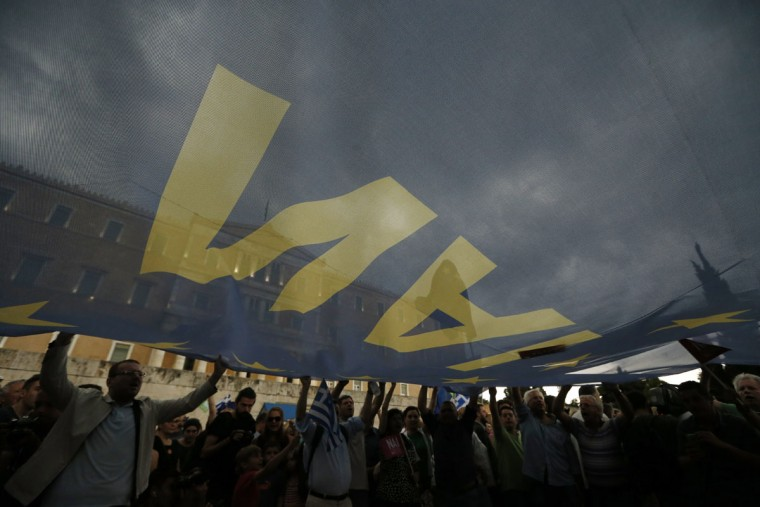 Demonstrators hold a giant European Union flag with the word ''YES'' on it during a rally organized by supporters of the YES vote to the upcoming referendum in Athens, Tuesday, June 30, 2015. (AP Photo/Daniel Ochoa de Olza)