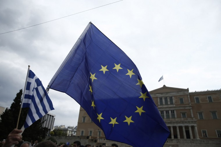 A demonstrator holds a European Union and Greek flag during a rally by supporters of the YES vote to the upcoming referendum, at Syntagma Square in Athens, Tuesday, June 30, 2015. (AP Photo/Daniel Ochoa de Olza)