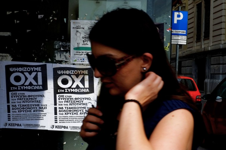 A woman passes by posters for the NO vote in the upcoming referendum, in central Athens, on Tuesday, June 30, 2015. (AP Photo/Petros Karadjias)