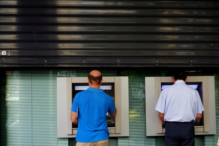 Men use the ATM outside of a closed bank five days before the upcoming referendum, in central Athens, on Tuesday, June 30, 2015. (AP Photo/Petros Karadjias)