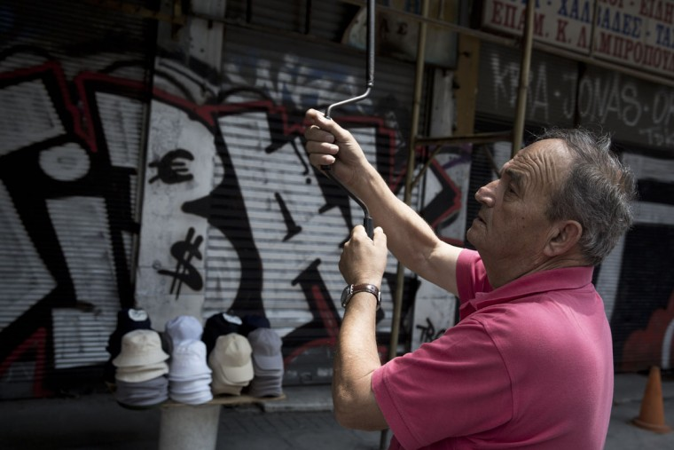 A man lowers the shutters of his clothes shop as at the background shutters are painted the Euro and the US dollar sign in central Athens on Tuesday, June 30, 2015. (AP Photo/Petros Giannakouris)