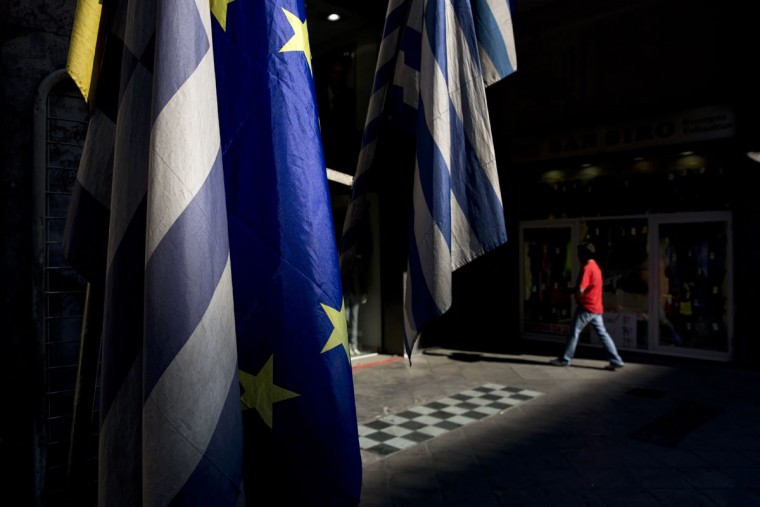 A man walks past European and Greek flags in central Athens, on Tuesday, June 30, 2015. (AP Photo/Petros Giannakouris)