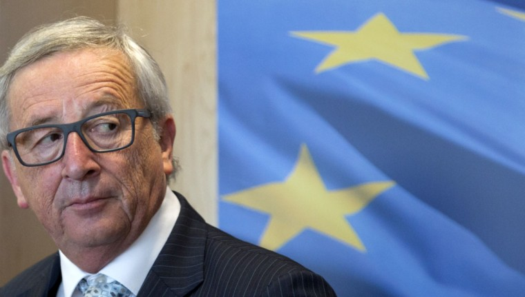 European Commission President Jean-Claude Juncker stands in front of a poster of the EU flag in his office at EU headquarters in Brussels on Tuesday, June 30, 2015. Juncker made a last-minute offer to Greece on Monday. Under that proposal, Tsipras would need to write to Juncker and other leaders saying he accepts the latest creditors' offer. He would also have to change his position on Sunday's referendum. (AP Photo/Virginia Mayo)