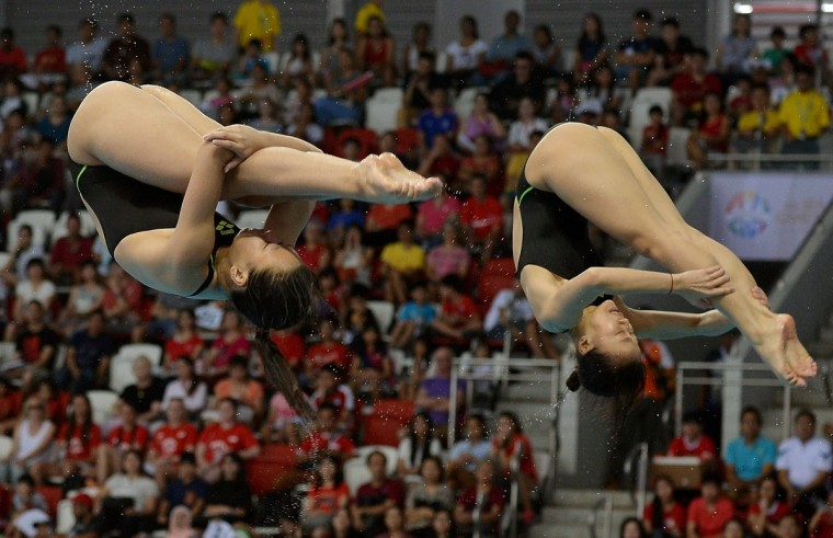 Hoang Le Thanh Thuy and Ngo Phuong Mai of Vietnam compete in the women's 3m synchronised springboard diving final during the 28th Southeast Asian Games (SEA Games) in Singapore on June 8, 2015. (MANAN VATSYAYANA/AFP/Getty Images)