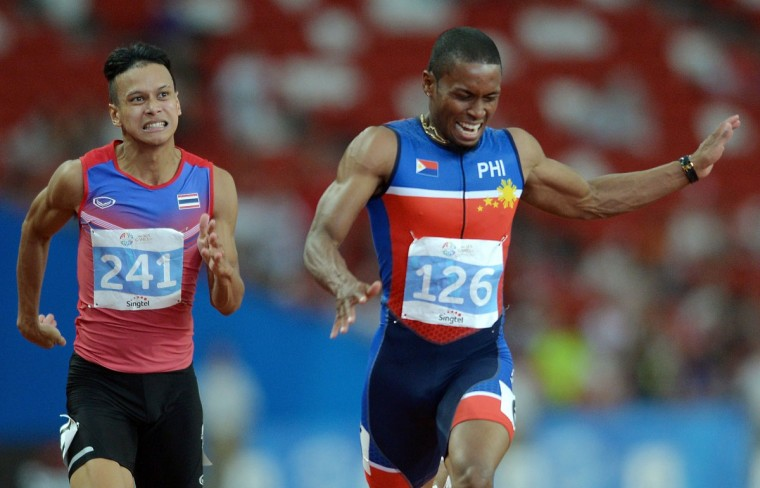 Eric Shauwn Cray of the Philippines crosses the finish line ahead of Jirapong Meenapra of Thailand in the men's 100m final athletics event during the 28th Southeast Asian Games (SEA Games) in Singapore on June 9, 2015. (MANAN VATSYAYANA/AFP/Getty Images)