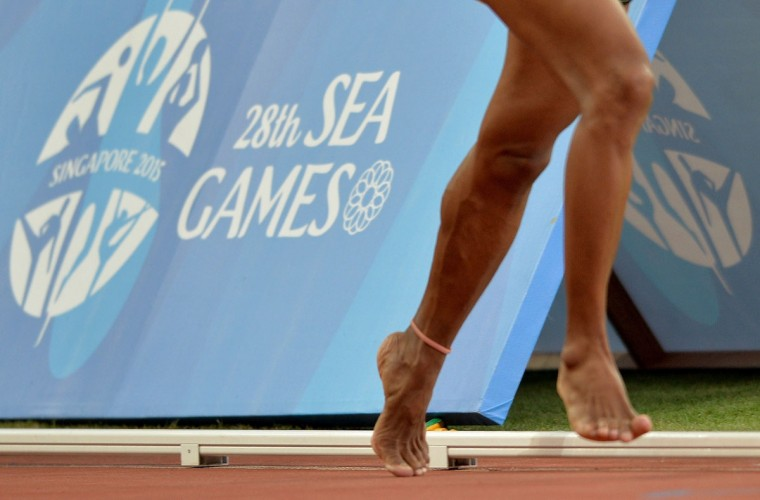 Pa Pa of Myanmar runs barefoot in the women's 5000m final athletics event during the 28th Southeast Asian Games (SEA Games) in Singapore on June 9, 2015. (MANAN VATSYAYANA/AFP/Getty Images)
