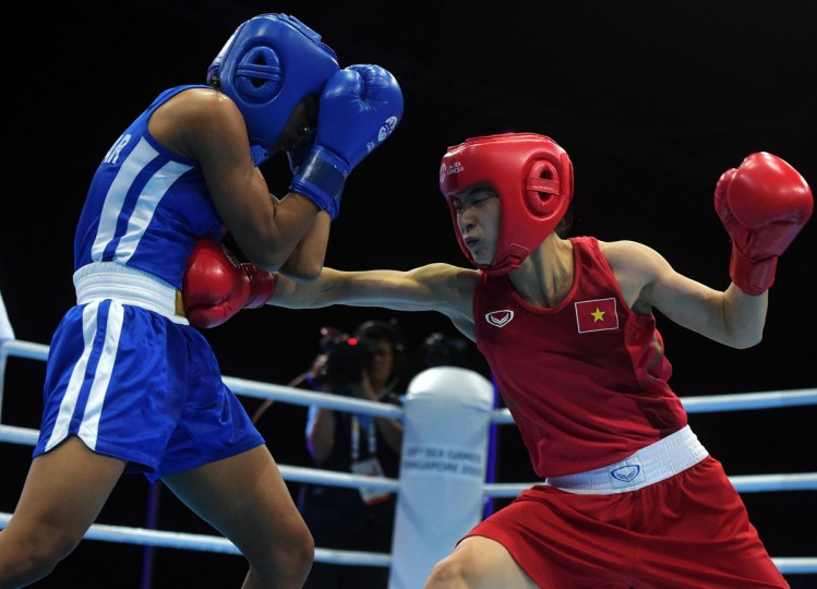 Vietnam's Le Thi Bang, right, lands a punch on Nwe Ni Oo, of Myanmar, during the Women's Bantam Weight (54kg) Semifinal Bout at the SEA Games in Singapore, Monday, June 8, 2015.(AP Photo/Joseph Nair)