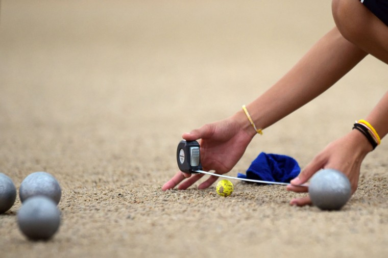 Bovilak Thepphakan of Laos measures the distance between the cochonnet and a boule in the Woman's Petanque Singles semifinal match at the SEA Games in Singapore, Monday, June 8, 2015.(AP Photo/Joseph Nair)