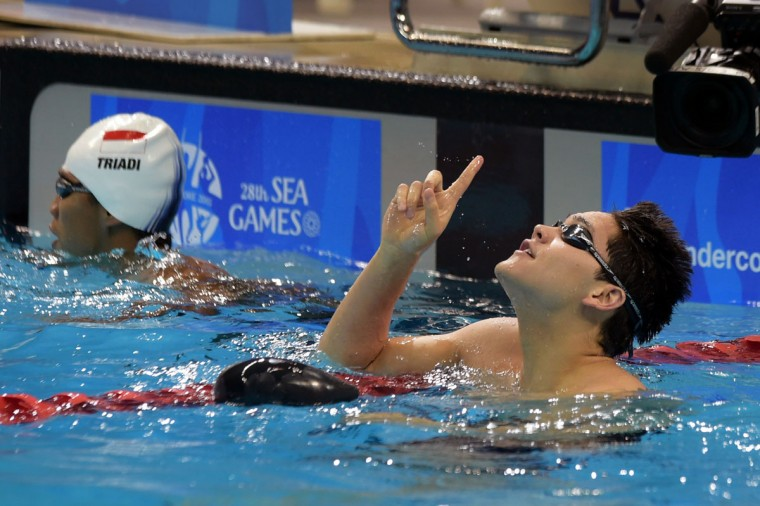 Singapore's Joseph Schooling, right, waves his finger at the sky after he wins the Men's 50m Freestyle at the SEA Games in Singapore, Monday, June 8, 2015.(AP Photo/Joseph Nair)