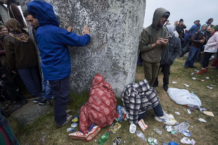 Revellers touch a megalith as they celebrate the pagan festival of Summer Solstice at Stonehenge in Wiltshire, southern England on June 21, 2015. The festival, which dates back thousands of years, celebrates the longest day of the year when the sun is at its maximum elevation. Modern druids and people gather at the landmark Stonehenge every year to see the sun rise on the first morning of summer. (NIKLAS HALLE'N/AFP/Getty Images)