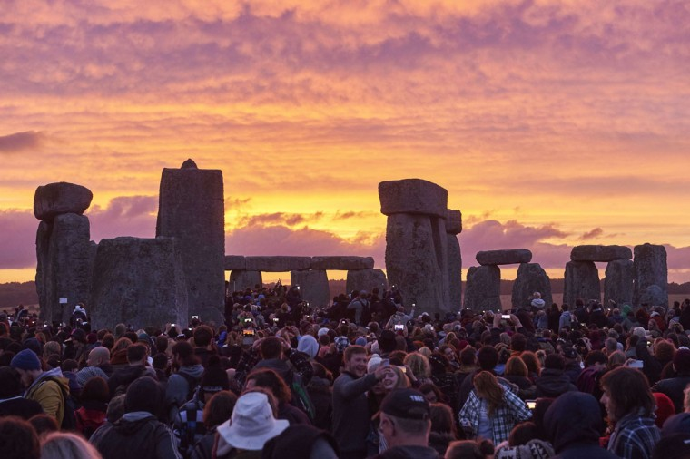 Revellers watch the sunrise as they celebrate the pagan festival of Summer Solstice at Stonehenge in Wiltshire, southern England on June 21, 2015. The festival, which dates back thousands of years, celebrates the longest day of the year when the sun is at its maximum elevation. Modern druids and people gather at the landmark Stonehenge every year to see the sun rise on the first morning of summer. (NIKLAS HALLE'N/AFP/Getty Images)