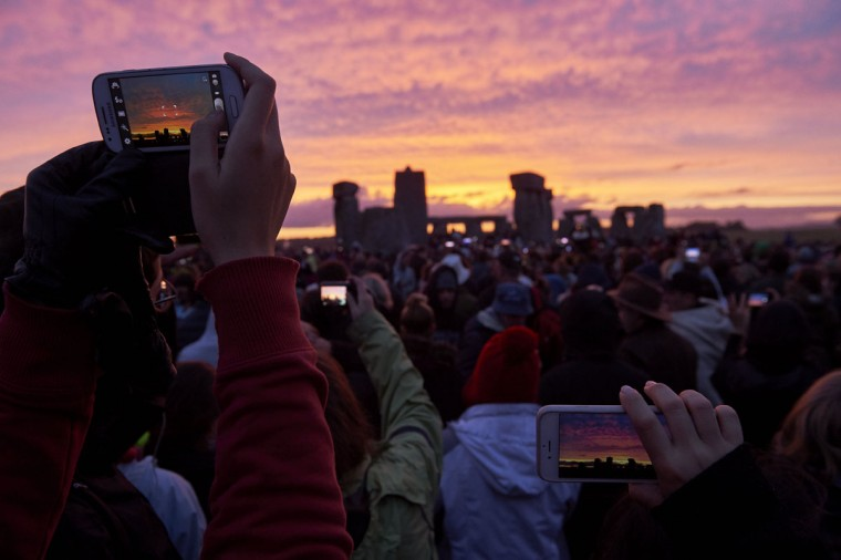 Revellers photograph the sunrise as they celebrate the pagan festival of Summer Solstice at Stonehenge in Wiltshire, southern England on June 21, 2015. The festival, which dates back thousands of years, celebrates the longest day of the year when the sun is at its maximum elevation. Modern druids and people gather at the landmark Stonehenge every year to see the sun rise on the first morning of summer. (NIKLAS HALLE'N/AFP/Getty Images)