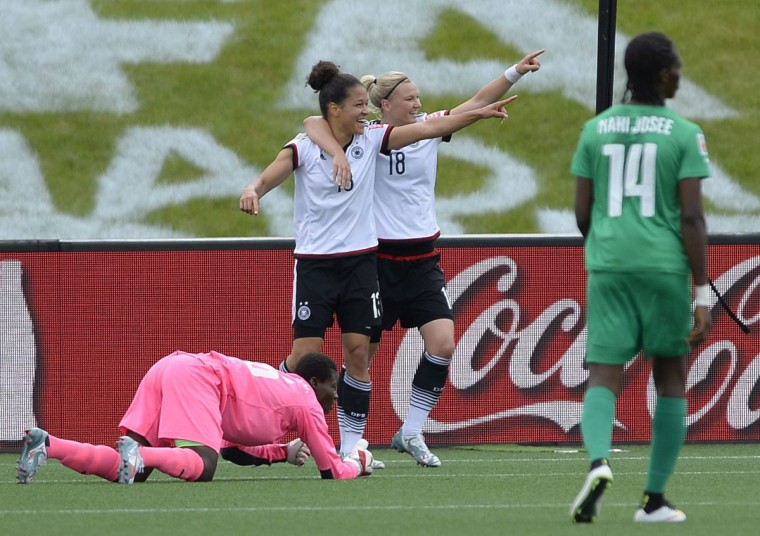 Germany's Celia Sasic celebrates her first goal with Alexandra Popp as Ivory Coast goaltender Dominique Thiamale and Josee Nahi look on during first half FIFA Women's World Cup soccer action in Ottawa, Ontario, Sunday, June 7, 2015. (Justin Tang/The Canadian Press via AP)