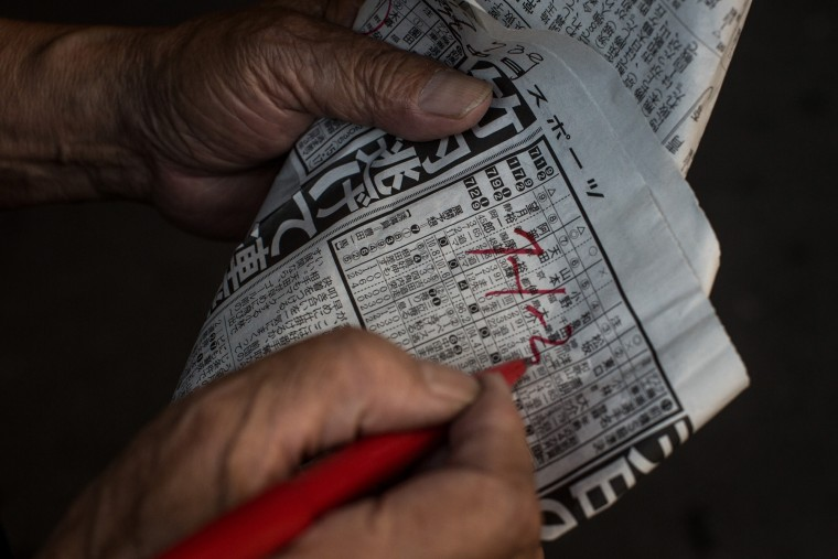 A punter writes down his picks on a form guide during the Keirin races at Kawasaki Velodrome on July 11, 2015 in Kawasaki, Japan. (Photo by Chris McGrath/Getty Images)