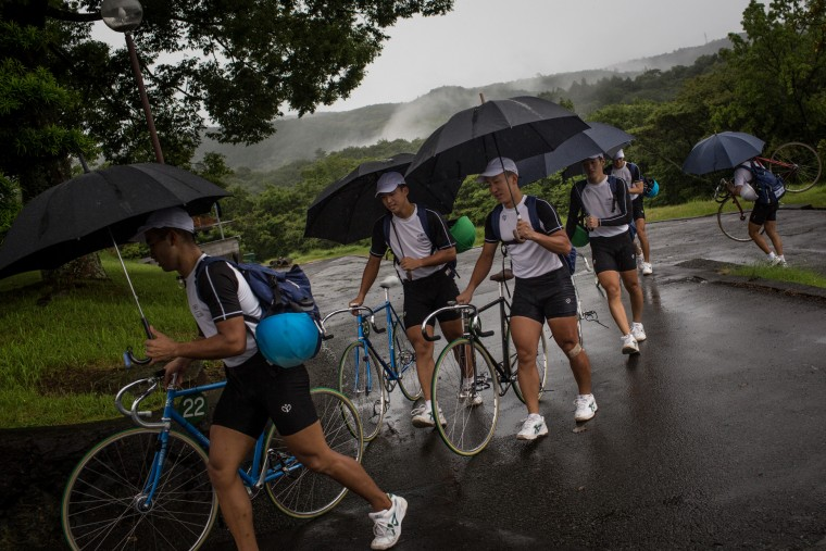 Keirin students walk back to the bike garage in the rain after the days training at the Nihon Keirin Gakkou (Japan Keirin School) on July 8, 2015 in Izu, Japan. (Photo by Chris McGrath/Getty Images)