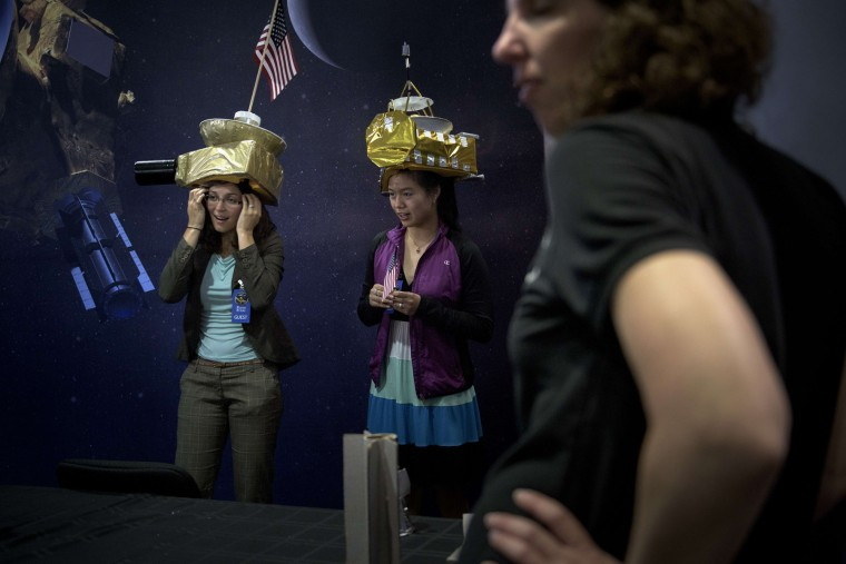People pose for photos wearing New Horizons probe hats at the Johns Hopkins University Applied Physics Laboratory July 14, 2015 in Laurel (AFP PHOTO/BRENDAN SMIALOWSKIBRENDAN SMIALOWSKI/AFP/Getty Images)