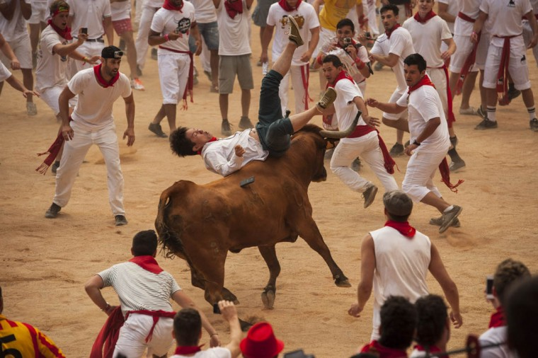 A reveler is pushed by a cow in the bull ring, at the San Fermin Festival, in Pamplona, Spain. (Alvaro Barrientos/AP photo)