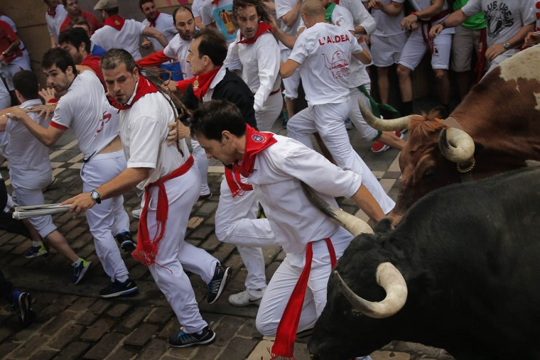 An 'El Tajo y La Reina' ranch fighting bull's horn touchs the arm of a reveler as they turn Estafeta corner during a running of the bulls of the San Fermin festival in Pamplona, Spain, Wednesday, July 8, 2015. Revelers from around the world arrive in Pamplona every year to take part on some of the eight days of the running of the bulls. (Daniel Ochoa de Olza/AP photo)
